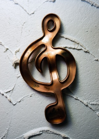 A treble-clef musical symbol on plastered wall.
