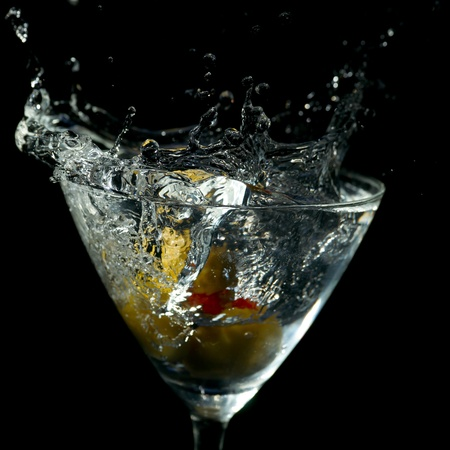 Water or other clear liquid splashes out of a Martini glass against black background.