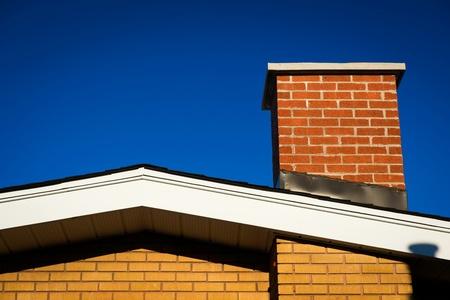 深い青色の空を背景の明るい日光でレンガの煙突とれんが造りの家の切り妻。