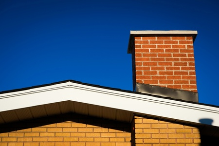 The Gable of a brick house with brick chimney in bright sunlight, against a deep blue sky.