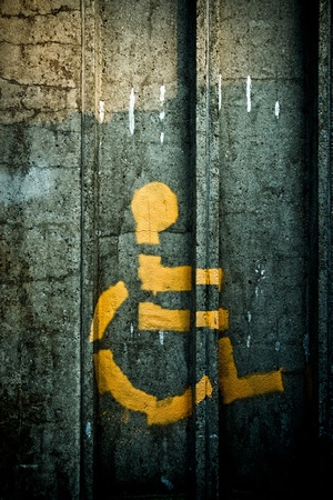 dingy: Symbol of person in wheelchair spray-painted onto a dark, old, decrepit stone wall.