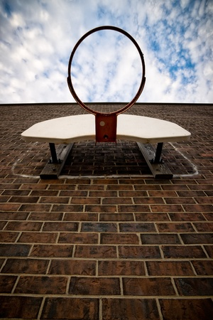 unusual angle: Unusual perspective shot looking up at a netless basketball hoop affixed to a brown, brick wall. Stock Photo