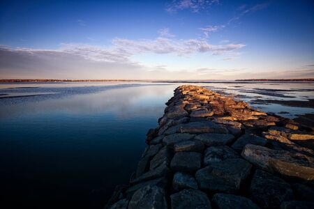 britannia: A stone jetty reaches toward the horizon on the calm waters of the Ottawa River near Britannia Beach in early morning light. Stock Photo