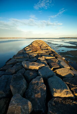 A long stone jetty stretches toward the horizon on the historic Ottawa River near Britannia beach. Stock Photo - 13037695