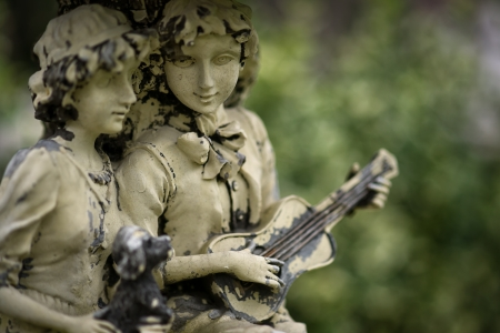 Old statue of a young couple in love - boy and girl, with boy playing musical instrument.
