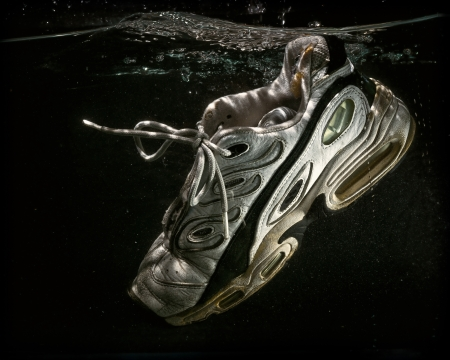 old shoes: A well worn and old tennis shoe floats submerged in water.