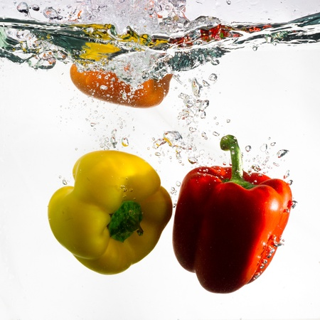 Two peppers, red and yellow, dropped into clear water against a white background.
