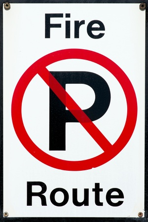 Universal no parking symbol sign with fire route notice text. photo