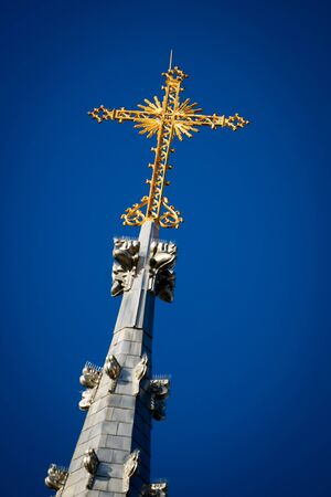 atop: An ornate golden cross sits against a clear, deep blue sky, atop the Notre Dame Cathedral Basilica in downtown Ottawa, Canada.