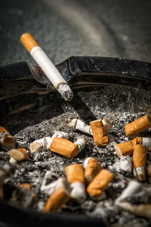 ashtray: A burning cigarette with long ash sits on the side of a full and very dirty ashtray full of cigarette butts.