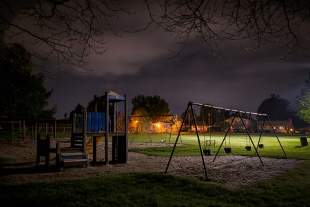 A creepy scene of a deserted childrens playground in a suburban park at night time.