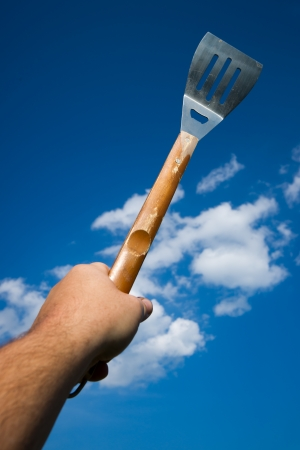 aloft: A male hand holds a BBQ spatula aloft against a blue sky with fluffy clouds.