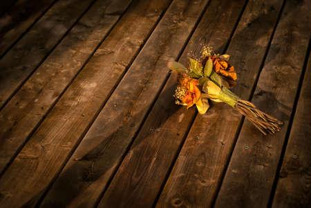 flores secas: Un viejo y decoloraci�n ramo de flores secas mentiras descartado en un piso de madera Foto de archivo