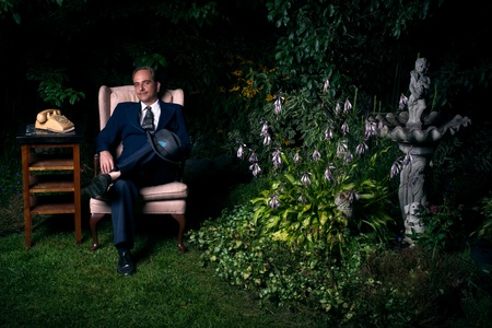 sits on a chair: A man wearing a suit sits on a chair beside a an old style rotary telephone in a lush, green garden  Stock Photo