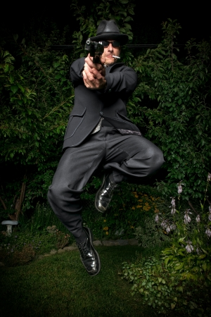 A man in an old style suit, hat and sunglasses jumps while pointing a gun. photo