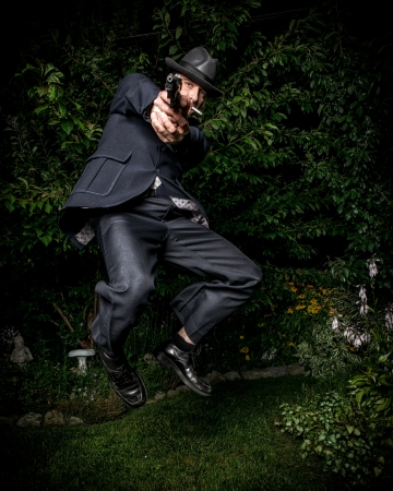 A man dressed in a vintage style suit and aiming a gun jumping in mid-air. photo