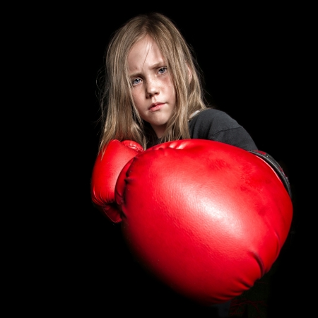 A young female child looks mean as she gets ready to throw a punch at the camera wearing boxing gloves