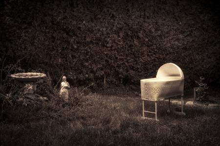 Bizar, vintage zoek foto van een griezelige, spookachtige babybed in een overwoekerde tuin