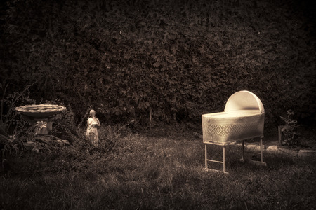 Bizarre, vintage looking photo of a creepy, spooky baby cradle in an overgrown garden