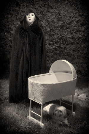 baby crib: Vintage looking photo of a creepy masked and cloaked person standing next to an eerie, empty baby crib