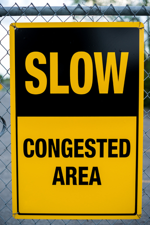 congested: A yellow caution sign reading  Slow - Congested Area hanging on a chain-link fence