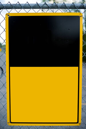 chainlink: A blank caution or warning type notice sign affixed to a chain-link fence - ready for your text