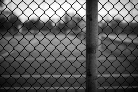 chain link fence: Black and white chain link fence background image with background blurred in a shallow depth of field