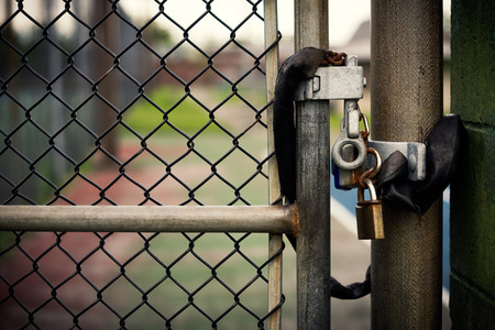 fencing wire: Closeup of a locked padlock securing a metal chain-link gate  Stock Photo