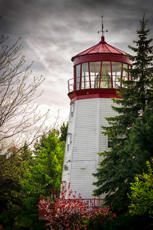 nestled: An old white and red, traditional looking lighthouse is nestled among thick, green foliage under stormy skies  Stock Photo
