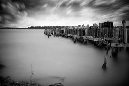 seaway: Long-exposure, black and white photo of the ruins of an old, abandoned pier reaching out into the serene waters of the St  Lawrence seaway
