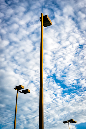 Three very tall lights, or lamps, of the kind to illuminate parking lots or park grounds stand against a cloudy sky