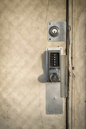 run down: An old, run down wooden door with multiple locks and a keypad entry security lock  Stock Photo