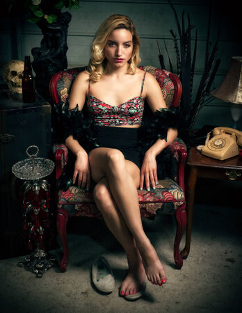 painted toenails: An attractive young blond woman sits in a chair and gazes alluring into the camera  Stock Photo