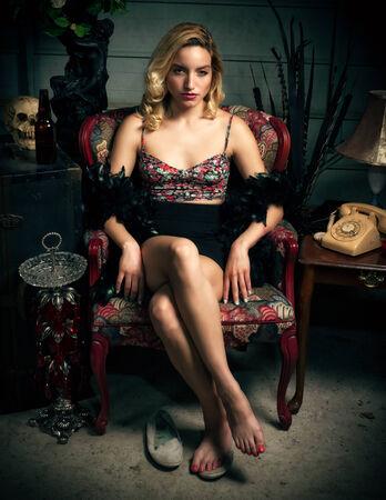pies sexis: Una joven y atractiva mujer rubia se sienta en una silla y mira seductora a la cámara Foto de archivo