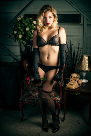 sex pose: A young, beautiful blond woman stands and gazes at the camera wearing sexy black bra, panties, fishnets, elbow gloves and heels  Stock Photo