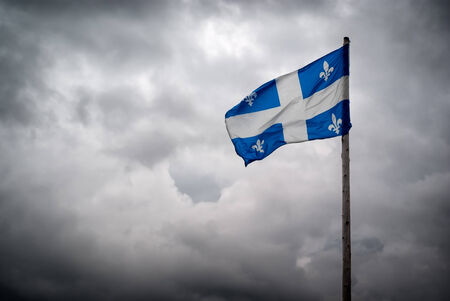 argent: The flag of Quebec   Fleurdelisé   waves in the wind in front of the tumultuous clouds of stormy skies
