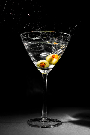 martini splash: Photo of a full martini glass with clear liquid and two olives with pimentos splashing into its contents