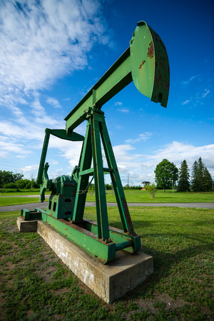 beam pump: Large, green, old and rusting antique, decommissioned oil pumpjack, sometimes called a pump horse, or oil horse, on display