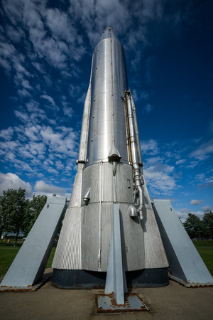 rocketship: Looking up from the base of a tall, stainless steel Atlas Rocket on supports as it stretches up into a deep, blue sky  Stock Photo