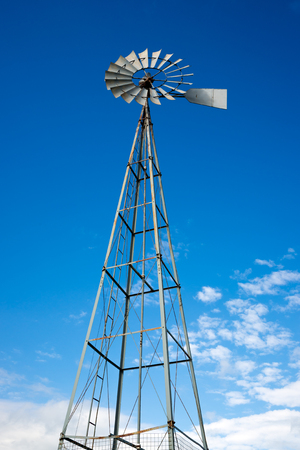 Looking up at an old style, antique tin water pumping windmill known as a Betty Pumper, against a bright, blue sky  Standard-Bild