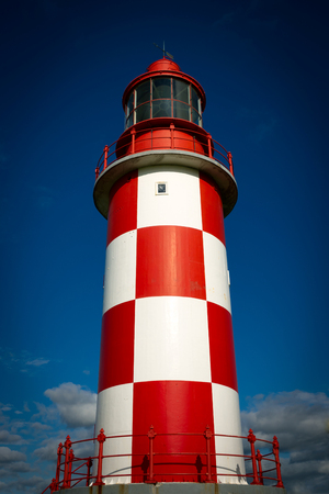 towering: A tall and towering red and white checkered lighthouse stands against a rich, deep blue sky