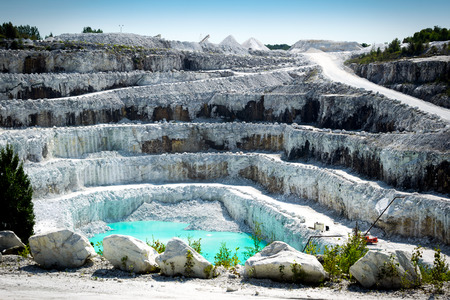 View of the rocky layers of a large and impressive open pit white marble stone mine.