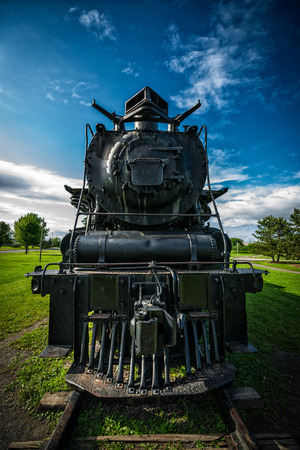 engine powered: An old, antique diesel powered 4-8-4 Northern style steam train locomotive as seen from directly in front of the engine. Stock Photo