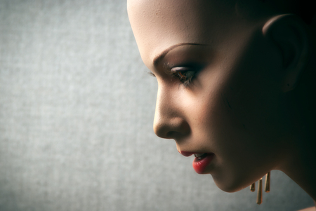 A slightly damaged and scratched female mannequin`s face shot in profile.