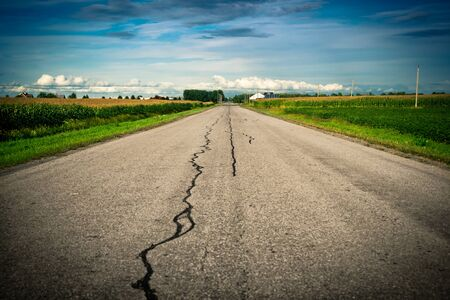 vanishing point: An old cracked, damaged and repaired country asphalt road stretches ahead toward its vanishing point on the distant horizon with corn fields on either side. Stock Photo