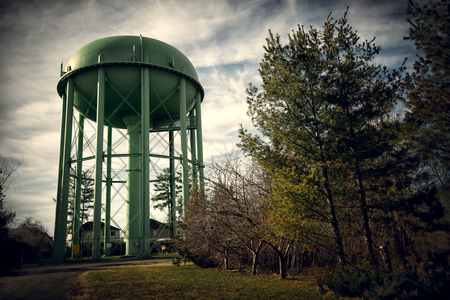 storage tank: An old, antique style tall green water tower or water storage tank standing high above trees and residential houses.