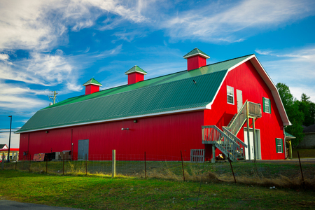 A long barn painted bright red with green roof under a bright blue sky in the country. Standard-Bild