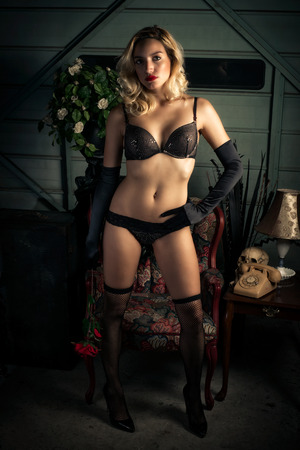 An attractive and young, sexy blond woman stands in a provocative pose wearing black lingerie. photo