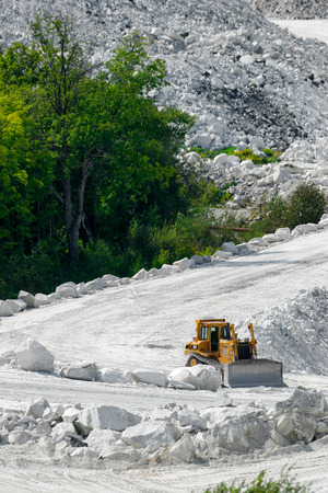 industrial park: A heavy, treaded bulldozer plow sits idle on the chalk white inclined road in a marble mine, ready to begin working. Stock Photo