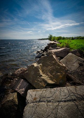 lawrence: Large boulders and line the shores of the St. Lawrence river in Ontario Canada.